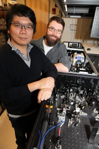 Graduate student Desmond Toa (left) and Jacob Dean, a postdoctoral research associate and lecturer in chemistry with the laser set-up, Credit: C. Todd Reichart